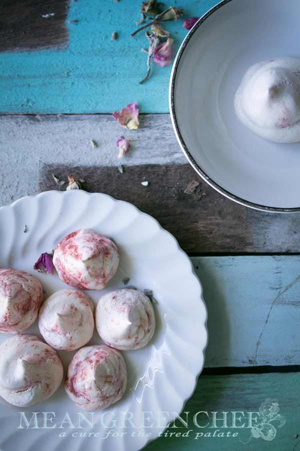 Overhead photo of Strawberry Meringue Cookies sitting on a white plate that's placed on old blue boards and sprinkled with flower petals.