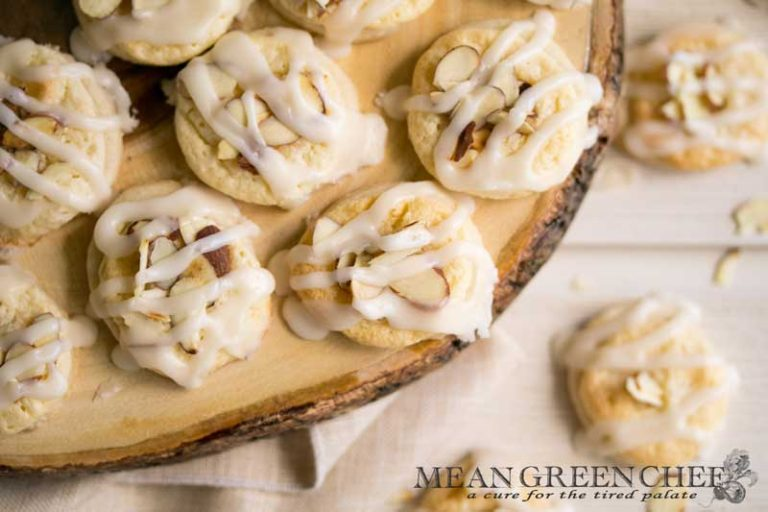 Overhead photo of Almond Pastry Cookies on white wooden background with roasted almonds sprinkled around.