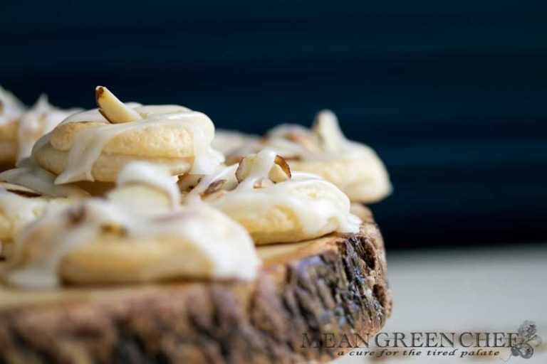 Almond Pastry Cookies on white wooden background with roasted almonds sprinkled around.