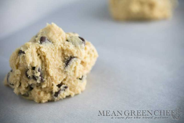 Bakery Style Chocolate Chip Cookie dough ready to be baked, sitting on a sheet pan lined with parchment paper.
