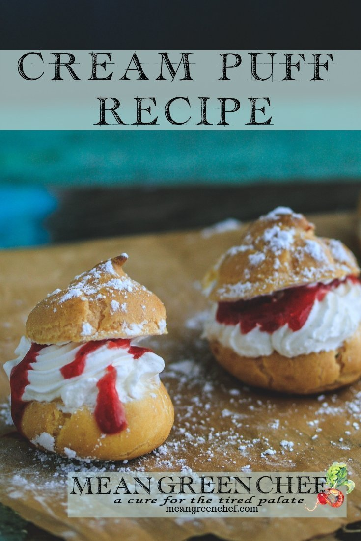 Cream Puffs with Strawberry Coulis shown with a sprinkling of powdered sugar on an old blue wooden background