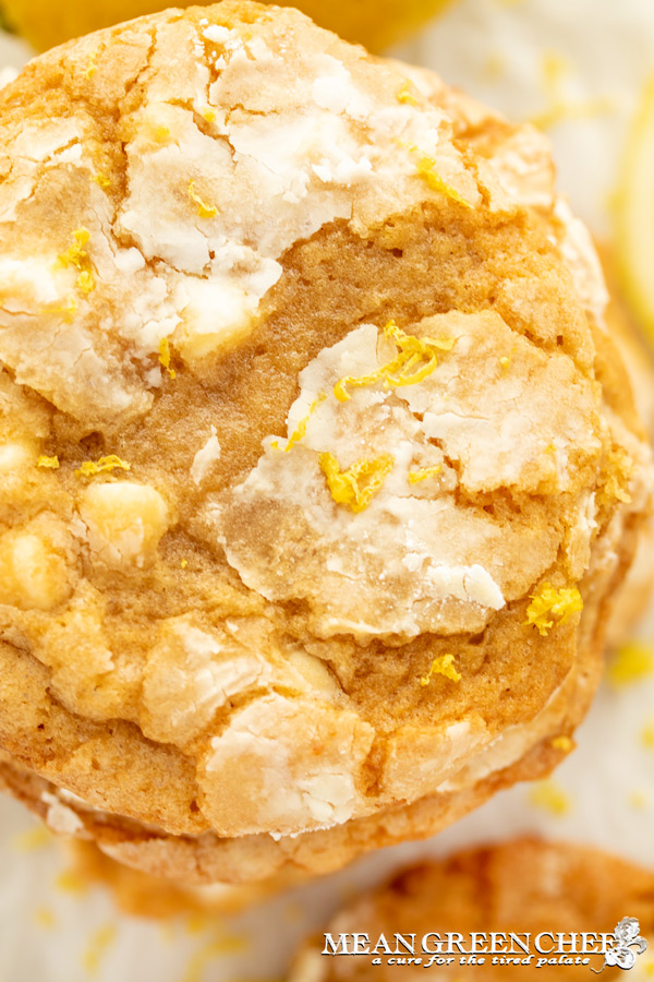 Meyer Lemon Cookies with fresh lemon zest on a white background and a lemon in the background.