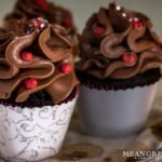 Side photo of Bakery Style Chocolate Cupcakes decorated with a high swirl of chocolate frosting red frosting berries and a sprinkle of silver stars in a scalloped gray and silver cupcake wrappers.