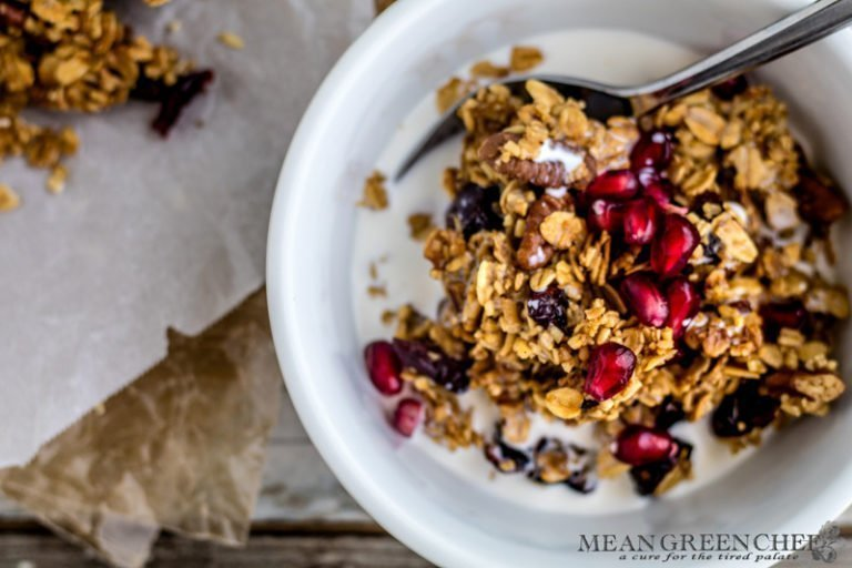 Overhead photo of a bowl of Brown Butter Granola in a white bowl garnished with pomegranate seeds on a wooden background. Mean Green Chef