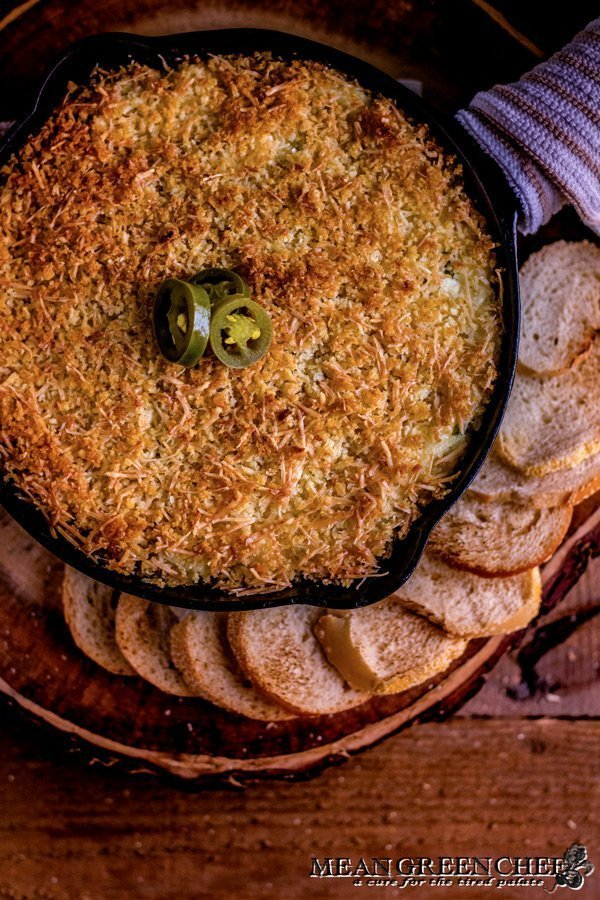 Overhead photo of Jalapeno Popper Dip in a cast iron pan surrounded with toasted sourdough bread rounds. on a rustic wooden background. Mean Green Chef
