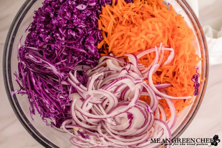 Ingredients for Red Cabbage and Carrot Slaw sliced in a large glass bowl on a white marble counter top background. Mean Green Chef