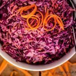 Overhead photo of Red Cabbage and Carrot Slaw in a large hit bowl with shredded carrots on a wooden background. Mean Green Chef