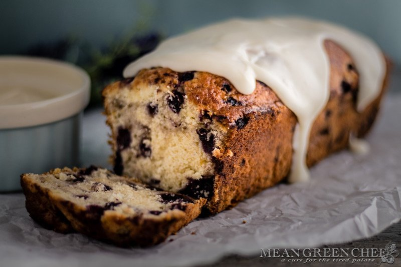 Side photo of Rustic Blueberry Banana Bread with a lush vanilla glaze dripping down a freshly sliced loaf. Mean Green Chef