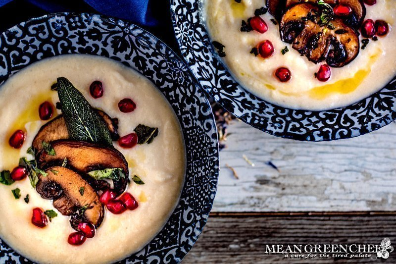 Creamy Cauliflower Bisque ladled into two blue bowls and garnished with smoked portobello mushrooms, fried sage, and pomegranate seeds.