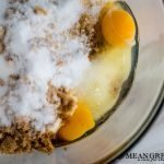 Ingredients for Best Ever Molasses Cookies brown and white sugar with eggs in a large glass bowl