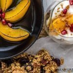 Overhead photo of Easy Peach Parfait with Brown Butter Granola, Roasted Pecans, and Cranberries in a short, stout glass. With a small cast iron pan int he upper left hand corner showing off browned peaches. Mean Green Chef