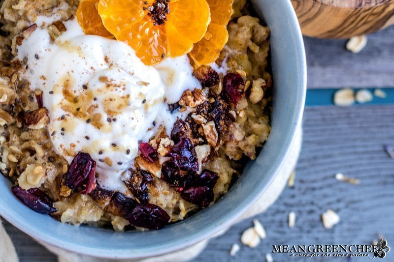 Overhead shot of a bowl of Spiced Mandarin Pecan Oatmeal garnished with whipped cream and Sumo Citrus.