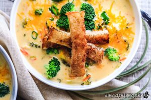 Bistro Broccoli Cheese Soup in large white bowls garnished with grilled sourdough bread.