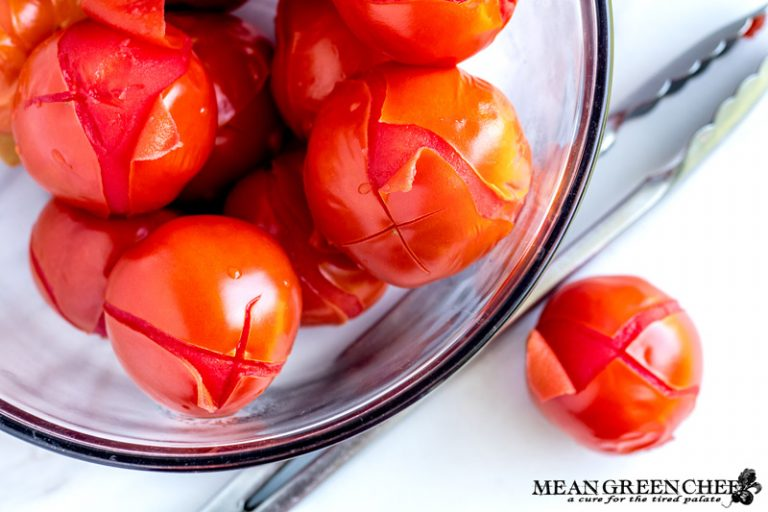Large glass bowl of red blanched tomatoes on a white marble counter top.