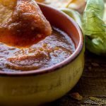 Restaurant Style Salsa in a yellow bowl with a freshly made tortilla chip being dipped.