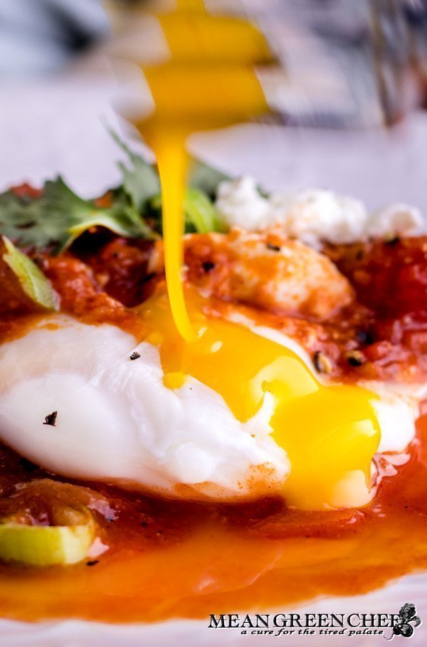 Shakshuka egg yolk being broken with a fork.