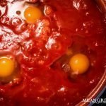 Eggs that are poaching in tomato sauce for Shakshuka.