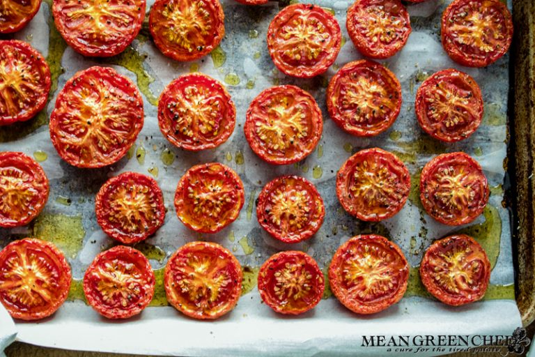 Slow Roasted Tomatoes on a sheet pan sitting in a sheet pan with parchment paper.
