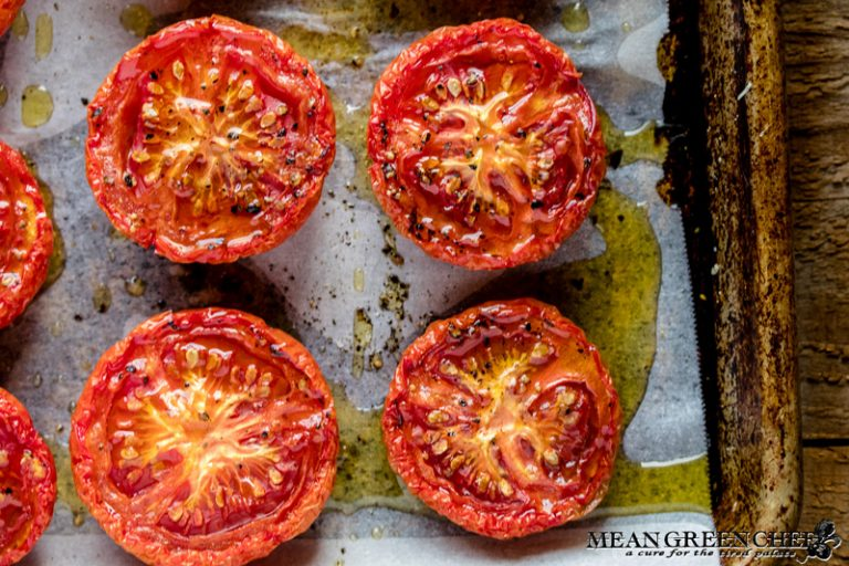 Sweet Slow Roasted Tomatoes on a sheet pan lined with parchment paper on a wooden background.