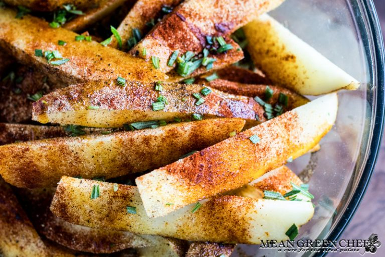 Potato wedges covered with olive oil, herbs and spices for oven baked fries.