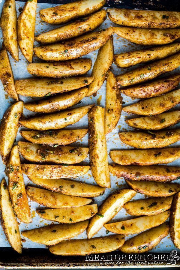 Sheet pan lined with parchment paper and potato wedges for Crispy Oven Fries.
