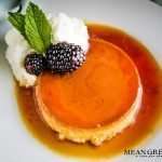 Classic Flan on a white plate with blackberries, whipped cream, and mint.