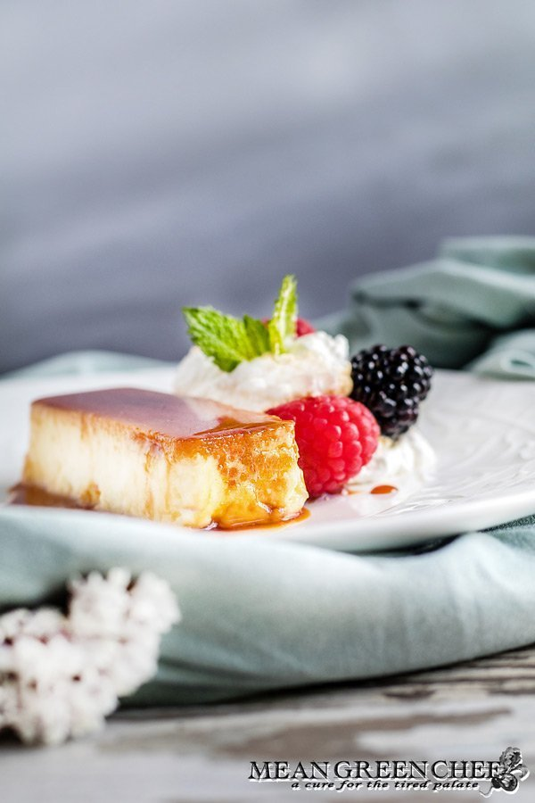 Classic Flan plated with berries and whipped cream.