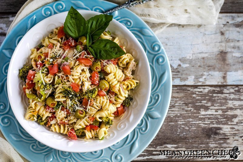 Italian Chicken Pasta Salad in a white bowl with fresh basil garnish.