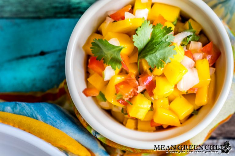Fresh mango salsa in a bowl on a old blue wooden background.