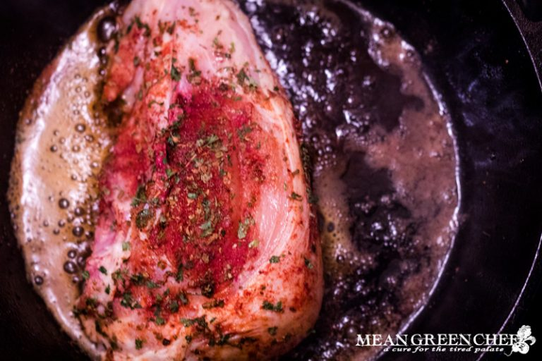 Blackened chicken cooking breast side down in a hot cast iron pan.