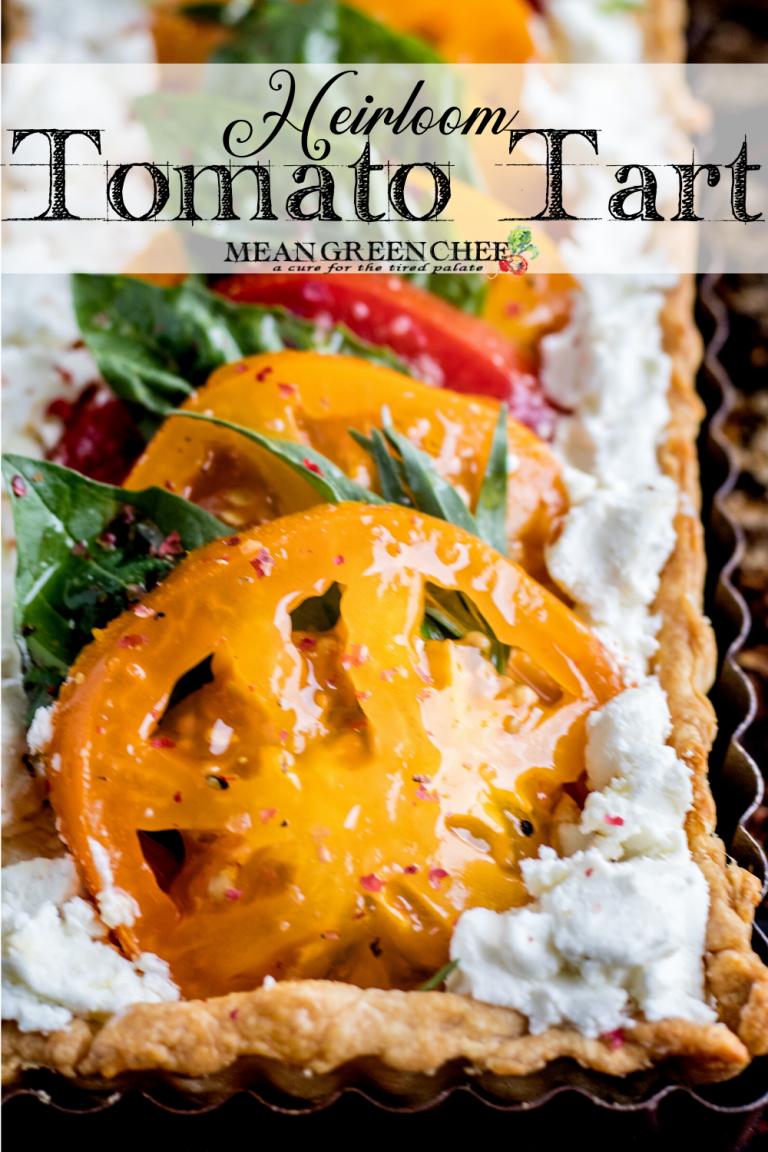 Heirloom Tomato Tart on a baking tray garnished with fresh basil.