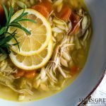 Lemon Chicken Orzo Soup in a light blue bowl, garnished with lemons.