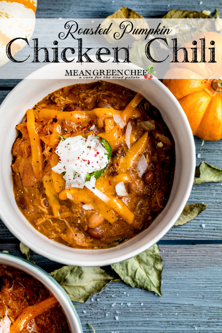 Pumpkin Chicken Chili in white bowl garnished with cheddar cheese and fresh avocado and jalapenos