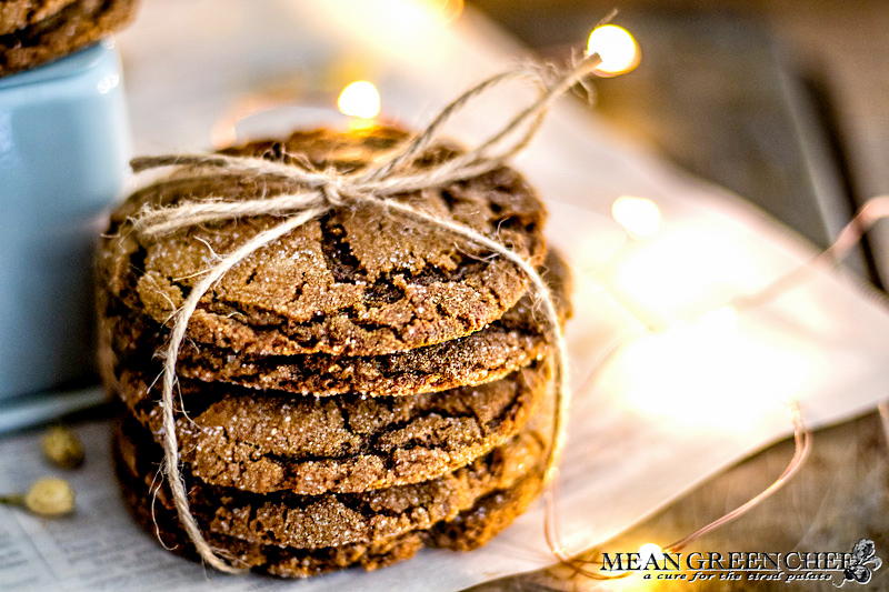 Stack of Molasses Cookies, tied with twine and sitting on newspaper that has been scattered with white flower buds