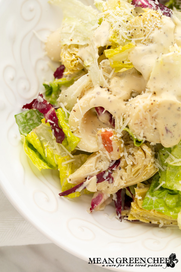 Close up of Big Easy Italian Salad in a white bowl garnished with fresh parmesan cheese