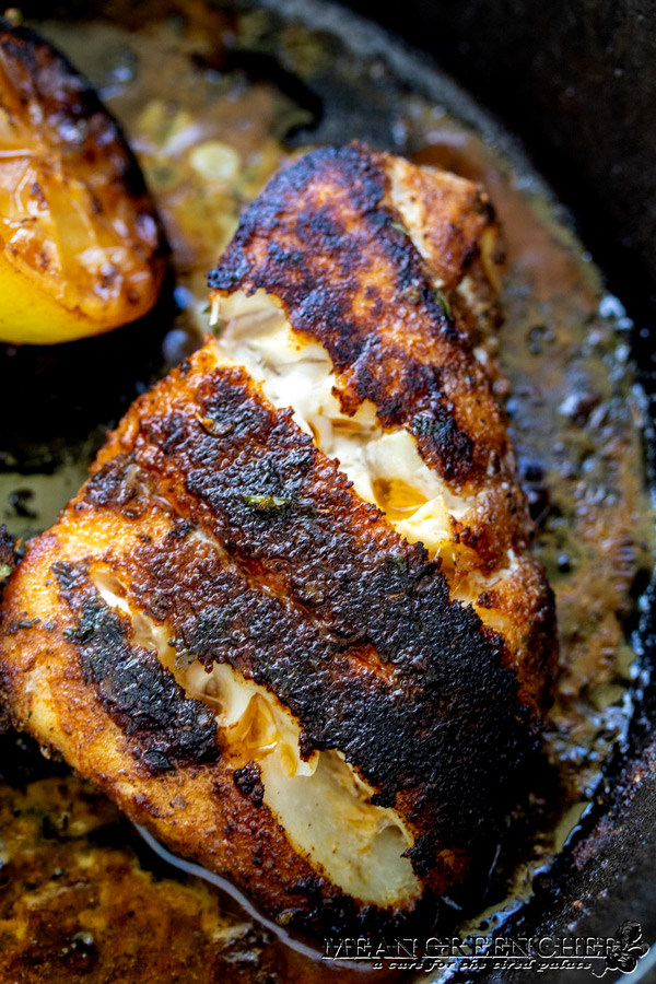 Gulfside Blackende Grouper cooking in a cast iron pan with lemon.